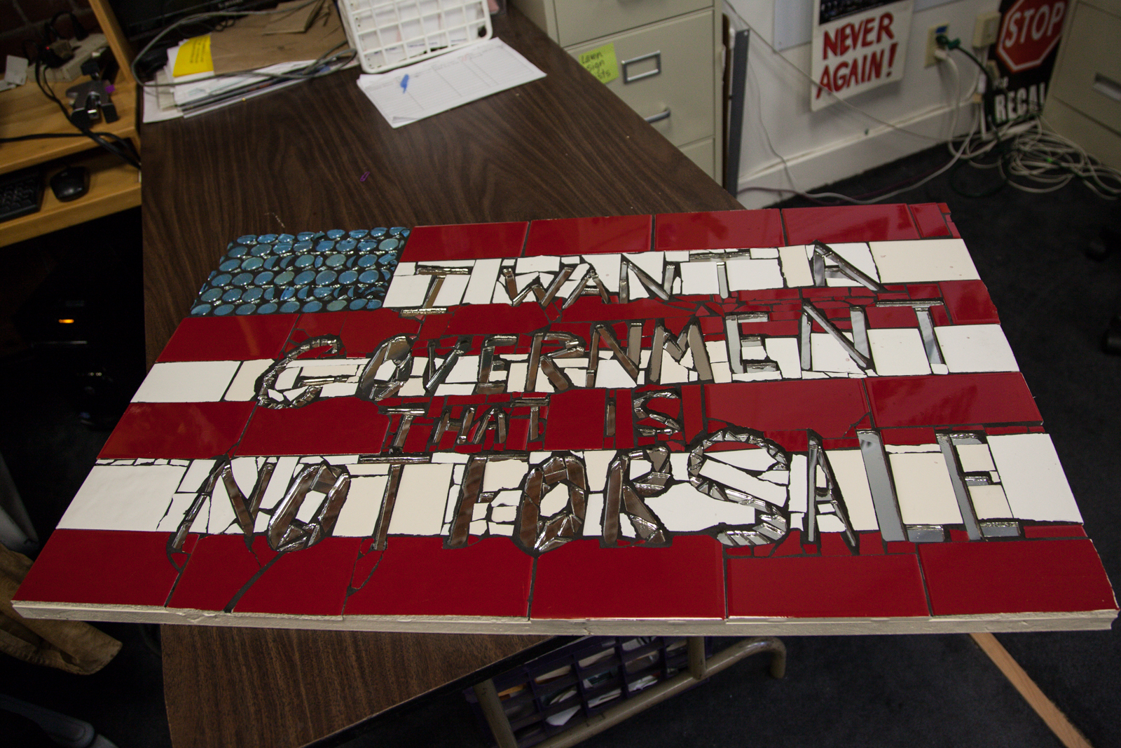 "A tile collage piece that says ""I want a government that is not for sale"""