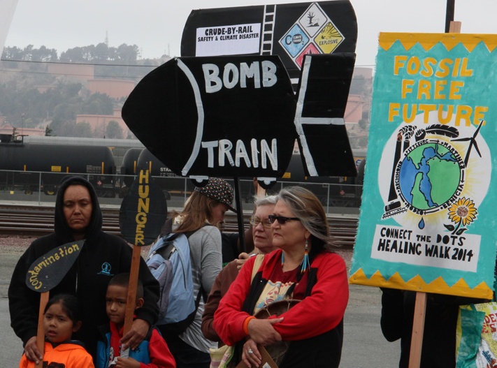 "Participants in an environmental protest in Richmond, CA with ""bomb train"" sign."