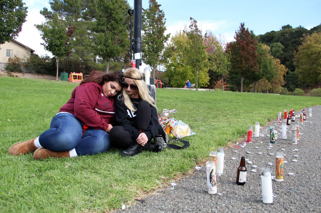 Melissa Sousa, left, and Shelby Ferguson sit by a makeshift memorial in La Moine Valley View Park where their friend Eric Brown of Richmond was fatally shot on October 10, 2016. Photo by Lauren Schwartzman.