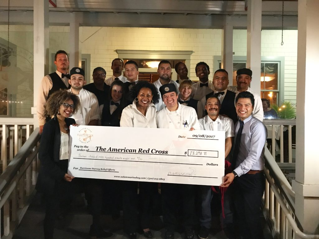 Saluté owner Menbe Aklilu and restaurant staff pose with a check for over $13,000 for Hurricane Harvey relief. Photo courtesy of Saluté e Vita Ristorante.