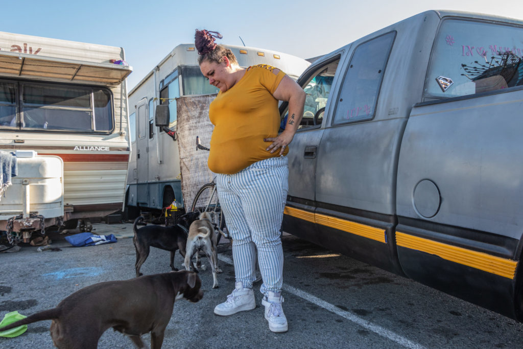 Amanda Jenkins watches her dogs play in an RV encampment on North Castro Street in Richmond, Calif.